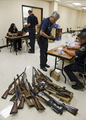 Detroit, Michigan - Police officers examine weapons turned in by residents in a gun buyback program. People were paid $25 to $200, depending on the type and quantity of weapons turned in. - Jim West - American,2010s,2011,adult,adults,America,American,americans,armed,buyback,buy-back,cash,cities,city,clj,crime,crime prevention,Detroit,enforcement,firearm,firearms,for,force,gun,gun control,guns,job,l
