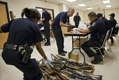 Detroit, Michigan - Police officers examine weapons turned in by residents in a gun buyback program. People were paid $25 to $200, depending on the type and quantity of weapons turned in. - Jim West - 30-08-2011