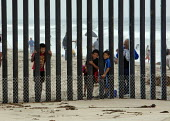 San Ysidro, California, children looking through the fence at Border Field State Park separating the USA and Mexico at a beach at the Pacific Ocean - Jim West - 03-07-2011