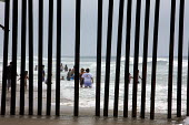 San Ysidro, California, the fence at Border Field State Park separating the USA and Mexico at a beach at the Pacific Ocean. Across the border, Mexican families play in the surf. - Jim West - 03-07-2011