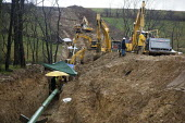 Workers building a natural gas pipeline in southwestern Pennsylvania where hydraulic facturing is commonly used to increase gas recovery. USA. laying the pipe in a trench. - Jim West - 29-11-2011
