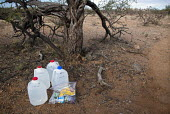 Water and food for Mexican migrants left along a desert trail by volunteers with No More Deaths. The faith based groups goal is to reduce the death toll among migrants who cross the desert to find wor... - Jim West - 2010s,2012,aid,America,american,american USA,americans,americas,Arizona,assistance,border,border control,border controls,border crossing,borders,bottle bottles,bottled,charitable,charity,christian chr