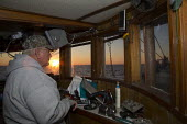 Mobile, Alabama - A shrimp trawler on Mobile Bay. Jackie Schwartz in the wheelhouse of the 52-foot Captain at sunrise. The trawler is part of the Alabama Fisheries Cooperative. - Jim West - 08-11-2012