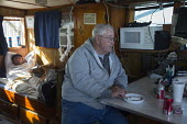 Mobile, Alabama - A shrimp trawler on Mobile Bay. While the nets are out, Jackie Schwartz (right) and Darrell Goleman take a break. Their workday begins at 500am and last until late afternoon. The tra... - Jim West - 08-11-2012