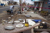 Union Beach, New Jersey - A man cleans up outside Jakeabobs Bay waterfront restaurant, which was heavily damaged by Hurricane Sandy. Someone has set an outdoor table with items salvaged from the storm... - Jim West - 28-11-2012
