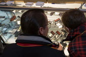 Milford, Michigan - A father and his son look over handguns as customers crowded the Huron Valley Guns store on Gun Appreciation Day. Pro-gun groups gathered at gun stores across the nation to buy wea... - Jim West - 19-01-2013