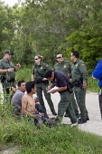Falfurrias, Texas - U.S. Border Patrol officers and a deputy sheriff question undocumented immigrants from Central America found hiding after a van holding 26 migrants crashed and overturned on Texas... - Jim West - 2010s,2013,accident,accidental,ACCIDENTS,adult,adults,agent,AGENTS,America,americans,arrest,arrested,ARRESTING,BAME,BAMEs,BME,bmes,Border,Border and Immigration Agency,border control,border controls,B