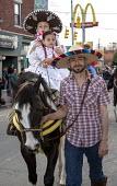 Detroit, Michigan - A family in traditional dress on a horse in the annual Cinco de Mayo parade in the Mexican-American neighborhood of southwest Detroit. - Jim West - 04-05-2014