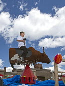 Detroit, Michigan - A boy rides a mechanical bull during the annual Cinco de Mayo parade in the Mexican-American neighborhood of southwest Detroit. - Jim West - American,2010s,2014,ACE,America,American,americans,AUTO,AUTOMOBILE,AUTOMOBILES,AUTOMOTIVE,boy,BOYS,bull,car,cars,celebrate,CELEBRATING,celebration,CELEBRATIONS,child,CHILDHOOD,children,Cinco,culture,d