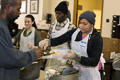 Detroit, Michigan - Volunteers from Young Detroit Builders serve a meal to the homeless and low-income individuals at the Open Door Ministry, a project of Fort Street Presbyterian Church. - Jim West - 23-01-2014
