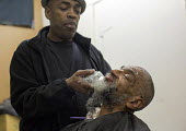 Detroit, Michigan - Barber Elvis Tucker giving a haircut and shaving a homeless man at the Open Door Ministry, a project of Fort Street Presbyterian Church. Open Door also offers a soup kitchen. - Jim West - &,2010s,2014,African American,African Americans,African-American,America,assistance,BAME,BAMEs,barber,belief,black,BME,bmes,charitable,charity,christian,christianity,christians,church,churches,convict