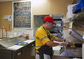 Los Angeles, California - A worker making a toasted sandwich at a fast food shop, Los Angeles - Jim West - American,2010s,2012,America,American,americans,Angeles,BAME,BAMEs,Black,BME,bmes,BREAK,California,capitalism,capitalist,catering,chef,chefs,cook,COOKERY,cooking,cooks,court,Diaspora,DINNER,dinners,DIN