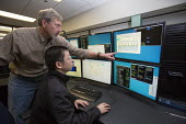 Batavia, Illinois - Jun Zhu (seated), associate professor at the Institute of Fluid Physics in China, and engineering physcist Elvin Harms, in the control room of the New Muon Lab at the Fermi Nationa... - Jim West - 05-11-2013