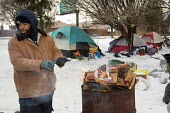 Detroit, Michigan - Charles (C.J.) Jones warms himself by a fire in a tent city that homeless people have established near downtown Detroit. About 2.5 percent of Detroit residents are homeless, even a... - Jim West - 09-01-2015