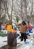 Detroit, Michigan - Charles (C.J.) Jones (right) stokes a fire with lighter fluid at a tent city that homeless people have established near downtown Detroit. About 2.5 percent of Detroit residents are... - Jim West - 09-01-2015