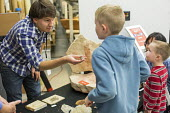 Salt Lake City, Utah - The Natural History Museum of Utah at the Rio Tinto Center on the University of Utah campus. A worker shows children rocks and fossils from the museum's collection. - Jim West - 15-11-2014