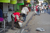 Oaxaca, Mexico - A man washes a cooking pot on the street near a large public market. - Jim West - 2010s,2015,americas,Amerindian,Amerindians,bought,buy,buyer,buyers,buying,cities,city,cleaning,cleansing,commodities,commodity,consumer,consumers,COOKERY,cooking,crowded,curb,customer,customers,dishwa