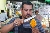 Oaxaca, Mexico - A man carves a mango into edible art for sale at a food stand. - Jim West - 17-01-2015