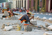 Oaxaca, Mexico - Workers use hammers and chisels to rebuild a cobblestone street. - Jim West - 2010s,2015,americas,Amerindian,Amerindians,BUILDING,BUILDINGS,by hand,chisel,Chisel and Hammer,cities,city,cobblestone,cobblestones,construction,Construction Workers,EARNINGS,employee,employees,Employ