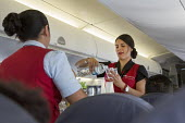 Mexico City, Mexico - Flight attendants serving drinks on an AeroMexico Connect flight to Oaxaca. - Jim West - 2010s,2015,AeroMexico,aeroplane,aeroplanes,air,air transport,aircraft,airline,airliner,airplane,airplanes,americas,Amerindian,Amerindians,attendant,ATTENDANTS,aviation,bottled,cabin,CABINS,cities,city