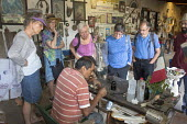 Ocotlan de Morelos, Oaxaca, Mexico - American tourists watch as Apolinar Aguilar Velasco engraves the blade of a hand-made knife in his workshop. - Jim West - 16-01-2015