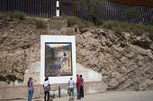 USA Mexico border tourists looking at Innocence At The Border, a painting by Ruben Daniels. It shows a boy, apparently trying to cross into the United States, riding a donkey towards death. Nogales, S... - Jim West - 16-10-2015