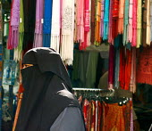 Muslim woman wearing a headcovering, a niqab, and a cloak, a jalbaab, in a London street market, UK - Luana Gomes - 2000s,2006,apparel,bought,burka,burkas,burqa,burqas,buy,buyer,buyers,buying,cloth,clothing,color colors,commodities,commodity,consumer,consumers,customer,customers,dress,East London,EBF Economy,GARMEN
