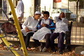Muslim boys wearing tofi, a crocheted cap, and tunics in east London. Texting on a mobile phone. - Luana Gomes - 20-08-2006