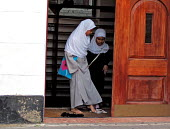 Muslim girls removing their shoes off before entering Madrasah, a school teaching Arabic and Qur'ranic studies, at a mosque in London, UK - Luana Gomes - 20-08-2006