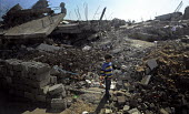 Palestinian boy standing among the rubble and wreckage of his home, Gaza City, Palestine, March 2009, following the attacks by Israel on Gaza during December 2008 and January 2009 which killed more th... - Mike Day - 10-03-2009