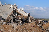 Palestinian men stand among the rubble and wreckage of a building, following Israels attack on Gaza during December 2008 and January 2009 which killed more than 1400 people. Gaza City, Palestine, Marc... - Mike Day - 2000s,2009,arab,arabs,attack,attacking,building,buildings,collapsed,conflict,conflicts,damage,damaged,DESTROYED,destruction,displaced,displacement,Gaza,homeless,homelessness,IDP,IDPs,internally,Intern