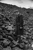 Miner Idris Moseley picking coal, riddling, for his pensioner neighbour at old tip or slag heap in Pontlottyn, South Wales during 1972 miners strike - Martin Mayer - ,1970s,1972,adult,adults,AGE,ageing population,coal,coalfield,dispute,DISPUTES,EARNINGS,ELDERLY,EQUALITY,Income,INCOMES,INDUSTRIAL DISPUTE,inequality,living wage,low pay,Low Income,low paid,low pay,Ma