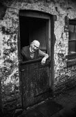 Retired miner Charles Clark, 90, at the doorway of thje last inhabited cottage in row of old National Coal Board cottages, Blackwood, South Wales. He had lived there since 1914 and had taken part in t... - Martin Mayer - ,1970s,1972,adult,adults,age,ageing population,Blackwood,coal,coalfield,cottage,COTTAGES,deprivation,disputes,doorway,elderly,EQUALITY,excluded,exclusion,fire,fires,HARDSHIP,house,houses,housing,impov
