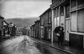 Woman with headscarf and umbrella returns home with shopping basket in wet weather, Blaenavon, South Wales - Martin Mayer - 1970s,1972,Blaenavon,bought,buy,buyer,buyers,buying,coalfield,commodities,commodity,consumer,consumers,Corner Shop,cottages,customer,customers,dark,drizzle,drizzling,EBF,Economic,Economy,EQUALITY,excl