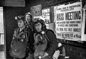 Exhausted miners rescue crew waiting to return down the pit to attempt a further rescue of trapped miners in the flooded Lofthouse colliery next to a poster advertising a union mass meeting about wage... - Martin Mayer - 1970s,1973,accident,accidental,accidents,accidents at work,advertising,and,BAD,breathing apparatus,Coal Industry,Coal Mine,coalindustry,collieries,colliery,conditions,crew,danger,dangerous,dangers,dea