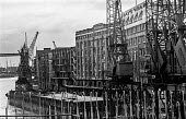 Some cranes still standing as others are broken up outside Hays Wharf and Chamberlains Wharf during the demolition of the old London wharves as containerisation starts - Martin Mayer - 1980s,1987,broken,capitalism,capitalist,Chamberlain's Wharf,cities,city,containerisation,crane,cranes,demolish,DEMOLISHED,demolishing,demolition,derelict,DERELICTION,developer,developers,DEVELOPMENT,d