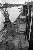 A crane by Chamberlains Wharf, near Tower Bridge is dismantled during the closure of the old London wharves and docks due to containerisation - Martin Mayer - 06-10-1987