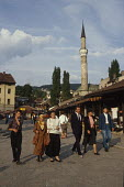 Walking through Sarajevo Old Town, Bosnia, with The Gazi Husrev-bey Mosque behind the market. Muslim headscaves were less common then. - Martin Mayer - 07-09-1990