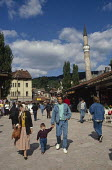 Young family walking through Sarajevo Old Town, Bosnia, with The Gazi Husrev-bey Mosque behind the market. Muslim headscarves were less common then. - Martin Mayer - 07-09-1990