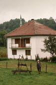 Elderly Muslim peasant woman outside her house in the Bosnian countryside - mosque in distance. - Martin Mayer - 10-09-1990
