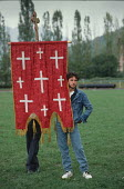 Denim clad supporter of the Bosnian Serb nationalist party - the Serb Democratic Party - with an Orthodox Christian Church banner listening to a speech by leader Radovan Karadzi, election rally in Gor... - Martin Mayer - 10-09-1990