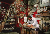 Maker of traditional copper and brassware at work in his shop in Sarajevo tourist district of Old Town, Bosnia. The sign behind him says Hand for Work and Peace - a hope that was later thwarted, Bosni... - Martin Mayer - 10-09-1990