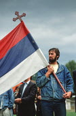 A denim clad, bearded supporter of the Bosnian Serb nationalist party Serbian Democratic Party waving a Serbian flag at an election rally in the Muslim majority town of Gorazde in Eastern Bosnia - Martin Mayer - 12-09-1990