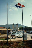 The Croatian flag flies in Medjugorje, western Bosnia (Herzegovina) with the church of St. James - pilgrimage centre for Our Lady of Medjugorje in the background - Martin Mayer - 12-09-1990