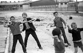 Boys posing as stone throwers in the Bogside, Derry, Northern Ireland 1971 shortly after the announcement of internment without trial - Martin Mayer - 1970s,1971,area,Armed Forces,army,Bogside,boy,boys,British Army,Catholic,catholics,child,CHILDHOOD,children,cities,city,communities,community,conflict,conflicts,confront,confrontation,confronted,confr