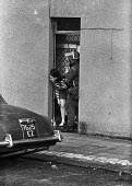 Young woman looking anxiously down the street in the Protestant Crumlin Road area, Belfast 1971 as a British soldier takes up position in her doorway after an incident when another soldier was shot - Martin Mayer - 14-08-1971