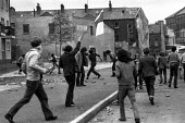 Stone throwing youths confronting British army, The Bogside, Derry, Northern Ireland, 1971 as one of their number waves the Irish tricolor flag, shortly after the introduction of internment without tr... - Martin Mayer - 1970s,1971,Armed Forces,army,Bogside,British,British Army,Catholic,catholics,cities,city,communities,community,conflict,conflicts,confront,confrontation,confronted,confronting,Derry,flag,flags,Ireland