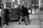 Stone throwing youths taunting British army from behind a burnt out car, The Bogside, Derry, Northern Ireland 1971 shortly after the introduction of internment without trial - Martin Mayer - 1970s,1971,Armed Forces,army,barricade,BARRICADES,Bogside,British,British Army,burnt,catholic,catholics,cities,city,communities,community,conflict,conflicts,confront,confrontation,confronted,confronti