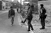 British soldier looking out anxiously for snipers in the Springfield Road area of Belfast on day 2 of internment without trial - Martin Mayer - 10-08-1971