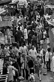 Brixton market, South London, summer 1970 - Martin Mayer - 1970s,afghan,afghans,BAME,BAMEs,black,BME,bmes,bought,Brixton,buy,buyer,buyers,buying,cities,city,coat,commodities,commodity,consumer,consumers,cultural,customer,customers,Diaspora,diversity,EBF,Econo